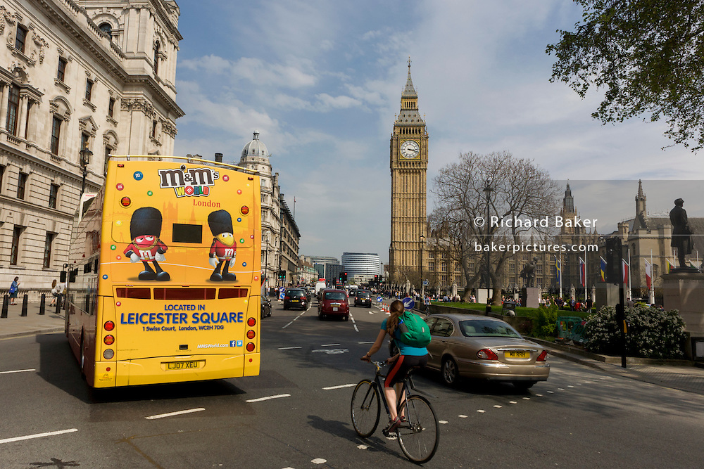 The M&M brand appears as an advert on the rear of a London tour bus travelling through the capital's streets, through Parliament Square.