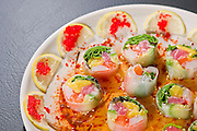A plate of sushi surrounded by lemon slices and roe.