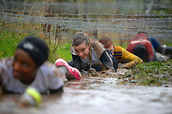 **EXCLUSIVE** ©  London News Pictures. 02/11/2013. Dani Emery, girlfriend of Manchester United footballer Ben Amos, climbs through mud under barbed wire. Wives and girlfriends of Premiership football players do part of the famous Tough Guy event in Wolverhampton, UK. Mandatory photo credit : Mike King/LNP
