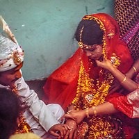 The groom first touches his bride at a traditional Bengali wedding in Dhaka, Bangladesh.