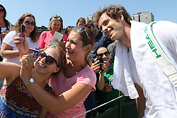 © London News Pictures. 09/07/2015. Andrew Murray allows fans to take selfies after a training session with coach Amelie Mauresmo a day before he plays Roger Federer in the semi finals at the Wimbledon Tennis Championships. Photo credit: LNP