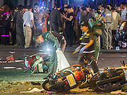 Aug. 17, 2015 - Bangkok, Thailand - <br /> <br /> Huge Explosion Rocks Bangkok Landmark<br /> <br /> A Thai police officer looks at one of the victims of the explosion at Erawan Shrine Monday. An explosion at Erawan Shrine, a popular tourist attraction and important religious shrine, in the heart of the Bangkok shopping district killed at least 19 people and injured more than 120 others, mostly foreign tourists, during the Monday evening rush hour. Twelve of the dead were killed at the scene. Thai police said an Improvised Explosive Device (IED) was detonated at 18.55. Police said the bomb was made of more than six pounds of TNT stuffed in a pipe and wrapped with white cloth. Its destructive radius was estimated at 100 meters. The Bangkok government announced that public schools would be closed Tuesday as a precaution.<br /> ©Exclusivepix Media