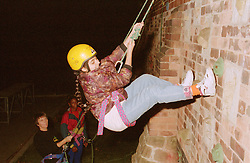 Teenage girl wearing safety helmet abseiling down brick wall,