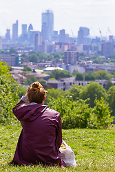 A woman admires the view of London's City skyline from Parliament Hill. London, May 26 2019.