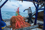 Luke, throwing the nets in to begin trawling. Luke is a Folkestone based fisherman out trawling for a 12 hour night shift on a fishing trip in his boat Valentine FE20, Hythe Bay, the English Channel, United Kingdom.