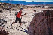SHOT 10/15/16 3:23:08 PM - Tossing a rock over the edge along the White Rim Trail. The White Rim is a mountain biking trip in Canyonlands National Park just outside of Moab, Utah. The White Rim Road is a 71.2-mile-long unpaved four-wheel drive road that traverses the top of the White Rim Sandstone formation below the Island in the Sky mesa of Canyonlands National Park in southern Utah in the United States. The road was constructed in the 1950s by the Atomic Energy Commission to provide access for individual prospectors intent on mining uranium deposits for use in nuclear weapons production during the Cold War. Four-wheel drive vehicles and mountain bikes are the most common modes of transport though horseback riding and hiking are also permitted.<br /> (Photo by Marc Piscotty / © 2016)