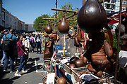 Boxing gloves for sale at Portobello Road Market in Notting Hill, West London, England, United Kingdom. People enjoying a sunny day out hanging out at the famous Sunday market, when the antique stalls line the street.  Portobello Market is the worlds largest antiques market with over 1,000 dealers selling every kind of antique and collectible. Visitors flock from all over the world to walk along one of Londons best loved streets.