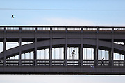 A pedestrian walks by the High Level Bridge on Tuesday, March 16, 2021 in Newcastle. It is a road and railway bridge spanning the River Tyne between Newcastle upon Tyne and Gateshead in North East England. It is considered the most notable historical engineering work in the city. It was built by the Hawks family from 5,050 tons of iron. (Photo/ Vudi Xhymshiti)