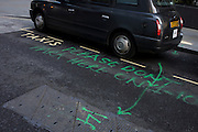 Sprayed parking notice on the ground in a City of London side street.