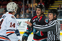 KELOWNA, CANADA - SEPTEMBER 22: Nic Holowko #14 of the Kamloops Blazers exchanges words with James Hilsendager #2 of the Kelowna Rockets as linesman Dustin Minty intervenes on September 22, 2017 at Prospera Place in Kelowna, British Columbia, Canada.  (Photo by Marissa Baecker/Shoot the Breeze)  *** Local Caption ***