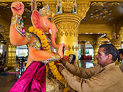 "05 SEPTEMBER 2016 - BANGKOK, THAILAND:  A Hindu priest prepares a statue of Ganesha on the first day of Ganesha Chaturthi celebrations at Shiva Temple in Bangkok. Ganesha Chaturthi also known as Vinayaka Chaturthi, is the Hindu festival celebrated on the day of the re-birth of Lord Ganesha, the son of Shiva and Parvati. The festival, also known as Ganeshotsav (""Festival of Ganesha"") is observed in the Hindu calendar month of Bhaadrapada. The date usually falls between 19 August and 20 September. The festival lasts for 10 days, ending on Anant Chaturdashi. Ganesha is a widely worshipped Hindu deity and is revered by many Thai Buddhists. Ganesha is widely revered as the remover of obstacles, the patron of arts and sciences and the deva of intellect and wisdom.     PHOTO BY JACK KURTZ"