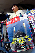 """A woman sells a magazine at a newsstand in Beijing, featuring a cover calling Taiwan's independence """"a dream"""" and depicting a warship launching missiles in the Taiwan Straights."""