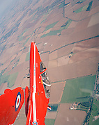 Climbing at sub-sonic speed, a Hawk jet aircraft of the elite 'Red Arrows', Britain's prestigious Royal Air Force aerobatic team, is seen from a neighbouring aircraft during an 'In-Season Practice' (ISP), a summer training flight over the farming fields of Lincolnshire. A landscape of agriculture is behind the red airplanes as they loop after a vertical climb. The front-seated pilot and his guest passenger stare through visors towards the wing to keep a perfect 'reference', maintaining an exact formation as seen from the ground. The Red Arrows fly to within 10 feet (3 metres) apart in some formations with speeds of 480 mph (770 kph), keeping in formation is a skill they learn every winter and refine on spare days like this between public air shows. The RAF roundel, (emblem), is on the nearest wing and the other fuselage as the world falls away in perspective.