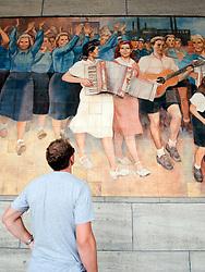 East German era socialist propaganda murals of happy workers on wall of German Finance Ministry building in Berlin Germany