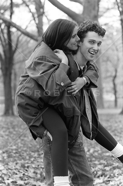 woman biting the ear of a man giving her a piggyback ride through the woods