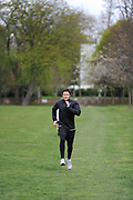 A man exercising in a park in London, UK. Fitness, exercise and wellbeing has never been more popular in the United Kingdom as people strive to live healthy lives.