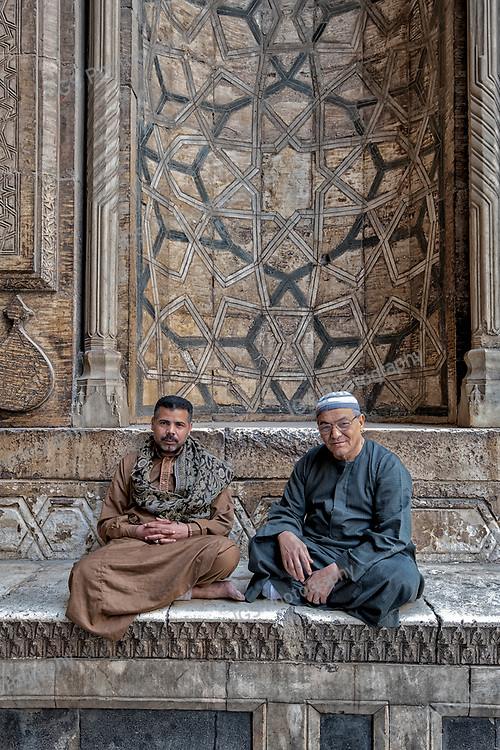 Caretakers sit at the entrance to the massive Mosque-Madrassa of Sultan Hassan in Islamic Cairo