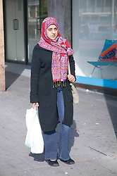 Woman walking back from shops with a carrier bag,