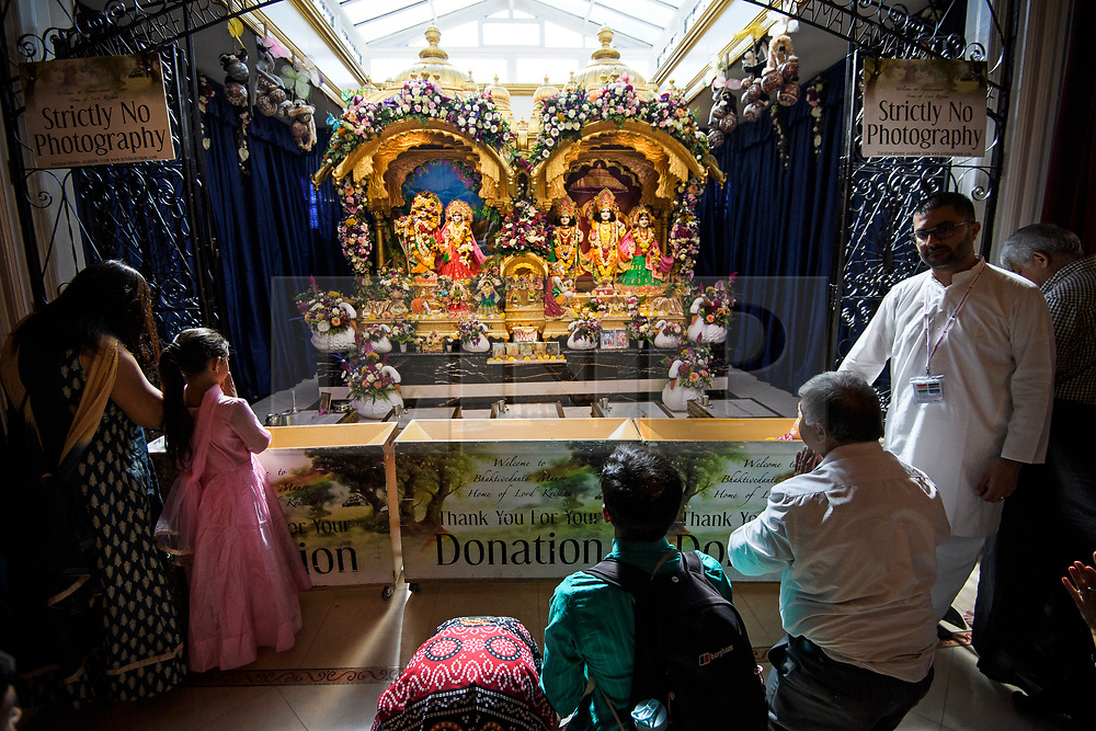 © Licensed to London News Pictures. 02/09/2018. Aldenham, UK. People worship in front of Statues of Hindu deities at Bhaktivedanta Manor Temple in Aldenham, Hertfordshire during the Janmashtami Hindu festival. Janmashtami is an annual Hindu festival that celebrates the birth of Krishna. Bhaktivedanta Manor, the venue fo the event, was donated to the Hare Krishna movement in February 1973 by former Beatle George Harrison. Photo credit: Ben Cawthra/LNP