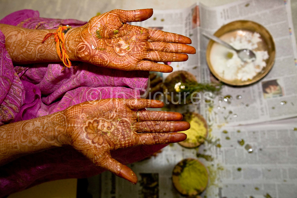 Shweta Singhal begins the preparations and rituals of her three day wedding ceremony in her home in Jaipur, here her Henna decorated hands have been smeared in saffron, dried tumeric, and vermillion, Rajasthan, India