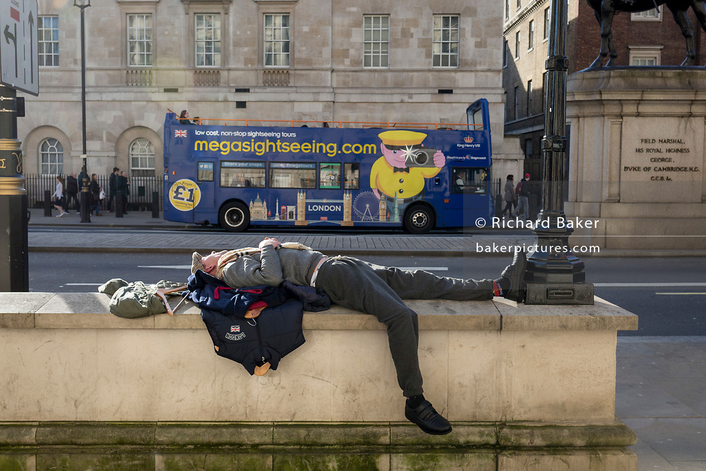 As a tour bus passes-by a man sleeps horizontally in Whitehall, Westminster, on 21st February 2019, in London, England.
