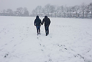 A couple walk hand in hand towards housing through snowbound public park in south London.