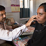 CAPTION: The Chamkol programme supports the government's response to the health and wellbeing of individuals with or at disk of disability. For Primary Health Centre (PHC) workers such as Dr Prasad, this means informal support during disability screenings, vaccination and immunisation outreaches. LOCATION: Panyadhundi (village), Kasaba (hobli), Chamrajnagar (district), Karnataka (state), India. INDIVIDUAL(S) PHOTOGRAPHED: Dr Prasad P.M. (left) and Navida Begum (right).