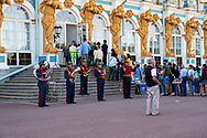 St Petersburg, Russia -- July 22, 2019.  Tourists line up to enter the Summer Palace; a marching band stands nearby.