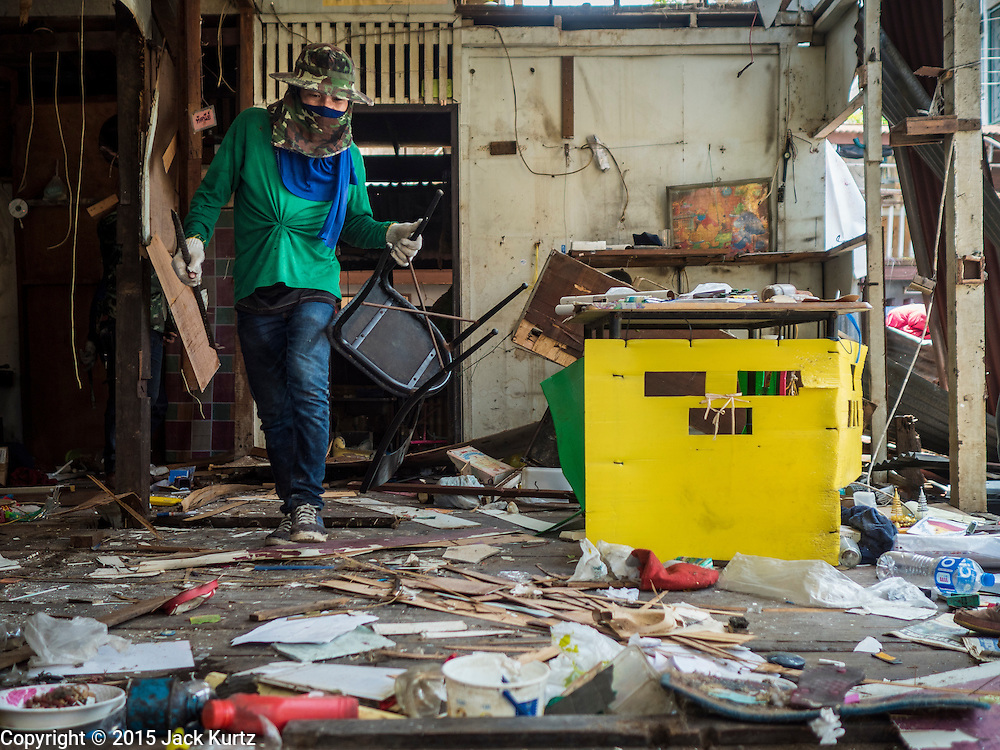 21 SEPTEMBER 2015 - BANGKOK, THAILAND: A demolition worker takes a dining room chair out of a home being torn down near Wat Kalayanamit. Fiftyfour homes around Wat Kalayanamit, a historic Buddhist temple on the Chao Phraya River in the Thonburi section of Bangkok are being razed and the residents evicted to make way for new development at the temple. The abbot of the temple said he was evicting the residents, who have lived on the temple grounds for generations, because their homes are unsafe and because he wants to improve the temple grounds. The evictions are a part of a Bangkok trend, especially along the Chao Phraya River and BTS light rail lines. Low income people are being evicted from their long time homes to make way for urban renewal.    PHOTO BY JACK KURTZ