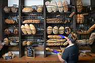 A cashier selects a loaf of bread for a patron at the Olde Hearth Bread Company store in Orlando, Fla., Tuesday, Feb. 9, 2016. (Phelan M. Ebenhack via AP)