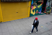 "The UK Chancellor Rishi Sunak has said it is ""very likely"" the UK is in a ""significant recession"" due to the Coronavirus pandemic lockdown, as figures show the economy contracting at the fastest pace since the financial crisis. And in the face of continued lockdown on the high street such as here on the Walworth Road in south London, a lone shopper walks past shuttered businesses, on 13th May 2020, in London, England."