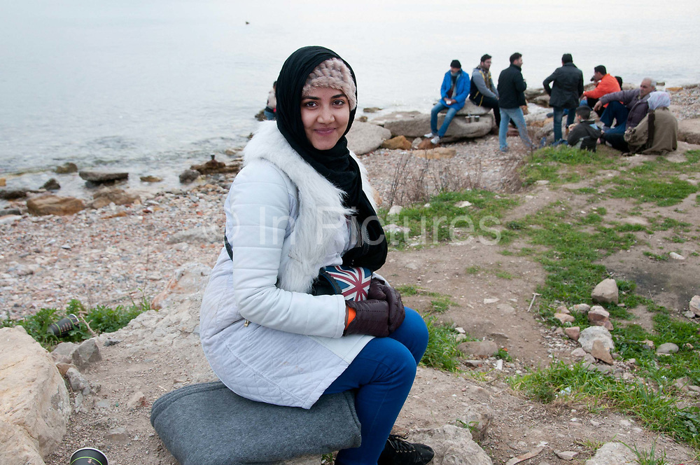 Greece . Chios Island, one of the places where refugees from Turkey land en route to Northern Europe. Newly arrived refugees relax on the beach next to Souda camp. A young woman smiles and holds a handbag with a Union Jack on it.