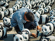 """04 MARCH 2016 - BANGKOK, THAILAND: A man takes pictures of the """"1600 Pandas+ World Tour in Thailand: For the World We Live In and the Ones We Love"""" exhibit on Sanam Luang in Bangkok. The 1600 paper maché pandas, an art installation by French artist Paulo Grangeon will travel across Bangkok and parts of central Thailand for the next week and then will be displayed at Central Embassy, a Bangkok shopping mall, until April 10. The display of pandas in Thailand is benefitting World Wide Fund for Nature - Thailand and is sponsored by Central Embassy with assistance from the Tourism Authority of Thailand and Bangkok Metropolitan Administration and curated by AllRightsReserved Ltd.     PHOTO BY JACK KURTZ"""