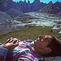 A hiker naps in a meadow beside a tarn below Mount Whitney in California's Sierra Nevada.