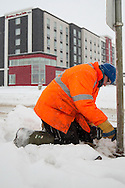 Photo Randy Vanderveen<br /> Grande Prairie, Alberta, Canada<br /> 2017-01-05<br /> Ryan LaCroix from the City of Grande Prairie's sign department reinstalls a sign that was either knocked down by a vehicle or snow removal equipment Hampton Inn & Suites. The one issue with sign damage is often it goes unreported by the offender and can have traffic safety implications.