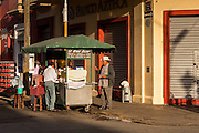 An elderly Mexican man buys food from a street vendor in Oaxaca, Mexico.