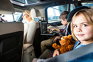 Family sitting in a car, the little girl on the backseat looking towards the camera