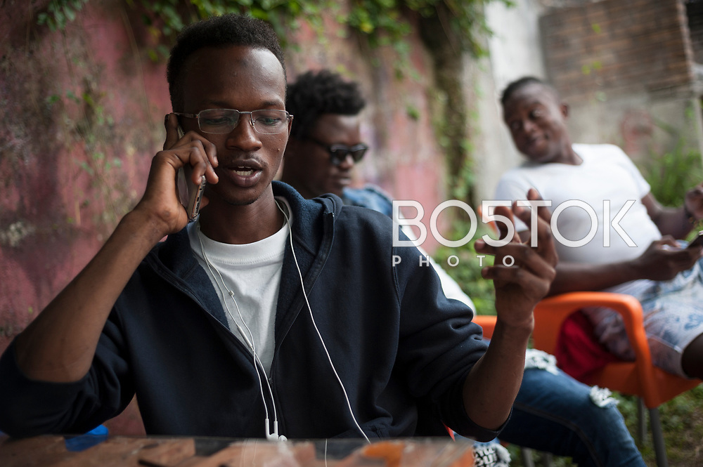 Amdi, an African migrant speaks on the phone with some other friends who are also in transit. Irun (Basque Country). September 4, 2018. Lakaxita is a self-managed socio-cultural space located in an occupied house, where volunteers have created a hosting network for migrants in transit who have already completed the 5-day period that can remain in public resources. This group of volunteers is avoiding a serious humanitarian problem Irún, the Basque municipality on the border with Hendaye. As the number of migrants arriving on the coasts of southern Spain incresead, more and more migrants are heading north to the border city of Irun. (Gari Garaialde / Bostok Photo)