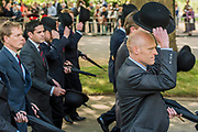 Bowlers are removed in salute as the march passes the memorial - The Combined Cavalry OCA Parade, Hyde Park. More than two thousand cavalrymen march in a mixture of uniforms or suits with bowler hats (for officers only) and furled umbrellas creating a quintessentially British scene. It is the 93rd Annual Parade and Service of The Combined Cavalry Old Comrades Association at the Cavalry Memorial adjacent and the Bandstand in Hyde Park. Field Marshal Baron Guthrie GCB, LVO, OBE, DL Colonel The Life Guards and Gold Stick took the salute at the march past for both serving and former soldiers of all the Regiments of Regular Cavalry and many Yeomanry Regiments.