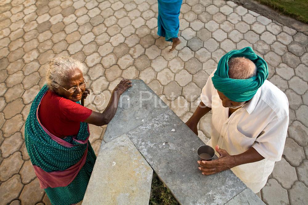Uthiradam and Vairakannu take a break for tea after their exercise session, Tamaraikulum Elders's Village, Cuddalore, Tamil Nadu, India