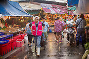 """26 SEPTEMBER 2012 - BANGKOK, THAILAND:   A porter walks through Khlong Toey Market in Bangkok. Khlong Toey (also called Khlong Toei) Market is one of the largest """"wet markets"""" in Thailand. The market is located in the midst of one of Bangkok's largest slum areas and close to the city's original deep water port. Thousands of people live in the neighboring slum area. Thousands more shop in the sprawling market for fresh fruits and vegetables as well meat, fish and poultry.   PHOTO BY JACK KURTZ"""
