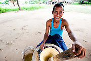 Portrait of a man grinding a paste in a pestle and mortar on the side of the road in Bagan, Myanmar. The paste is made into small cakes which are then fried and eaten soon afterwards.