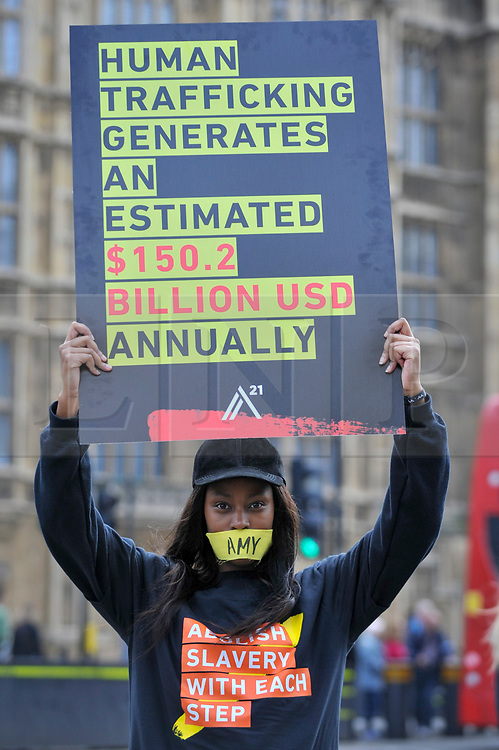 """© Licensed to London News Pictures. 14/10/2107. London, UK. A girl prepares to take part in the """"The Walk For Freedom"""", marching around the capital demonstrating against modern slavery.  The protest is co-ordinated with other walks which abolitionist group A21 is staging in 400 cities around the world on the same day. The facemasks represents the silence of modern slaves. Photo credit : Stephen Chung/LNP"""