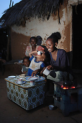 Tiblits' neighbors and her daughter Yirgalem, 18, granddaughter Samrawit, 1,  sit outside Tiblits' house enjoying a coffee ceremony  August 28, 2006 in Barentu, Eritrea. (Photo by Ami Vitale)