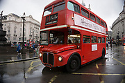 London, UK. Sunday 23rd August 2015. Heavy summer rain showers in the West End. People brave the wet weather armed with umbrellas and waterproof clothing. Routemaster bus now working as a place to have afternoon tea.