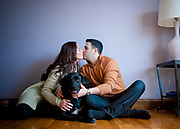 Man and woman kissing while seated on the floor with their dog