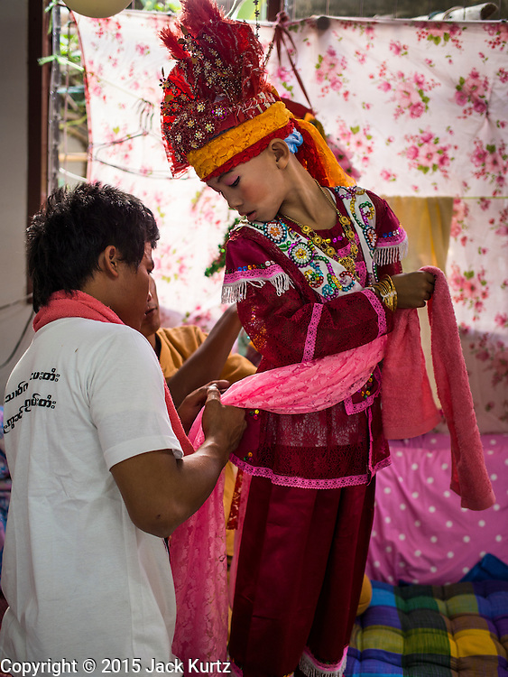 """04 APRIL 2015 - CHIANG MAI, CHIANG MAI, THAILAND:  Men help a boy get into his ceremonial outfit for the Poi Sang Long Festival at Wat Pa Pao in Chiang Mai. The Poi Sang Long Festival (also called Poy Sang Long) is an ordination ceremony for Tai (also and commonly called Shan, though they prefer Tai) boys in the Shan State of Myanmar (Burma) and in Shan communities in western Thailand. Most Tai boys go into the monastery as novice monks at some point between the ages of seven and fourteen. This year seven boys were ordained at the Poi Sang Long ceremony at Wat Pa Pao in Chiang Mai. Poy Song Long is Tai (Shan) for """"Festival of the Jewel (or Crystal) Sons.     PHOTO BY JACK KURTZ"""