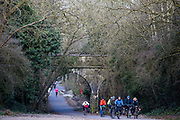 Cyclists and runners follow the restored 13 mile Bath Two Tunnel Greenway under a stone bridge on 6th April 2013.  They have attended the official opening of the iconic tunnels which provide a fantastic walking and cycling link between Central Bath, Midford, Monkton Combe and beyond. This development was started by a local community group and is part of the Sustrans lottery-funded project, Connect 2 Cycling Network.  Hundreds of people attended the event to enjoy the breathtaking views of the Somerset countryside. Bath, Somerset, United Kingdom.