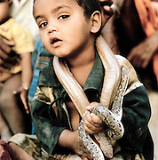 Young Boy holding a snake, Ghandhi Nager, Lucknow, Uttar Pradesh, India