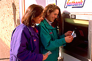 Tongan American sisters age 15 and 17 using outdoor cash machine.  St Paul Minnesota USA
